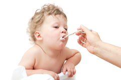 Small child with curly hair, the mother feeds with spoon Royalty Free Stock Image
