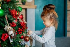 A small child decorates a Christmas tree in the house. The concept of a Merry Christmas, holiday, family.  Stock Images