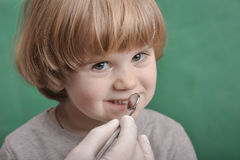 Small child and dental instrument Royalty Free Stock Images