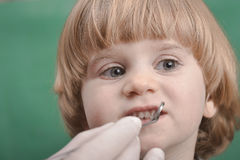 Small child and dental instrument Stock Photography