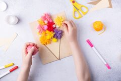 Small child doing a bouquet of flowers out of coloured paper and coloured knitting balls for mom