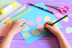 Small child doing a paper card. Child holds a pencil in hand. Card with paper air balloons, scissors, glue stick, colored paper Royalty Free Stock Image