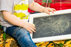 Small child draws with chalk Stock Image
