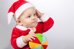 Small child dressed as Santa Claus. With a bright ball Stock Image