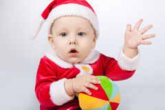 Small child dressed as Santa Claus. With a bright ball Royalty Free Stock Image