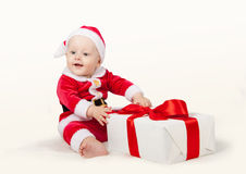 Small child dressed as Santa Claus. With a gift in a white box with red ribbon on white background Stock Photo