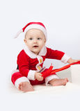 Small child dressed as Santa Claus. With a gift in a white box with red ribbon on white background Stock Images