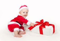 Small child dressed as Santa Claus. Kid with Christmas gift Royalty Free Stock Photography