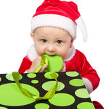 Small child dressed as Santa Claus. Tasting the package from the store on a white background Stock Images