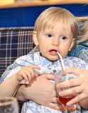 A small child drinks juice and sits on the hands of mom. royalty free stock photography