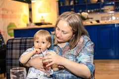 A small child drinks juice and sits on the hands of mom. stock photography