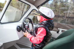 Small child driving motorboat as captain on deck Stock Photo