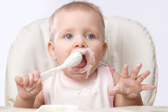 The small child  eating by himself Stock Images