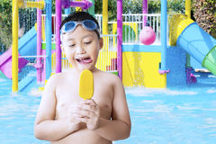Small child eating ice cream at pool Royalty Free Stock Photography
