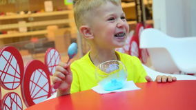 The small child eats blue icecream stock footage