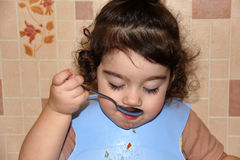 Small child eats, bringing spoonful to her mouth Royalty Free Stock Images