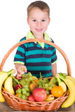Small child eats from the fruit basket Royalty Free Stock Photo