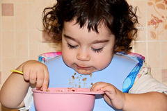 Small child eats himself with spoon Stock Photography