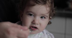 Small child is fed with a spoon.  stock footage