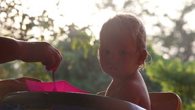 Small child fed at sunrise stock video footage