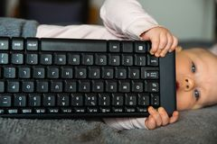 Small child, first steps on the internet, a newborn baby is holding a keyboard from the computer royalty free stock photo