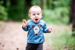 Small child in forest, shouting expression. Small child toddler in forest park outdoors, shouting expression stock photography
