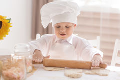 A small child in the form of a cook rolls the dough on a table Stock Images