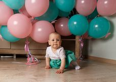 A small child, a girl, a baby, sits on the floor in a white and blue dress, against a background of blue and pink air, gel balls. royalty free stock photography
