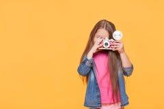 Small child girl holding retro camera and taking photo Royalty Free Stock Image
