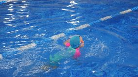 Small child girl is learning to swim in pool diving and floating in water. Child girl is swimming and diving underwater in pool. She is learning and training on stock video footage