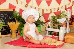 A small child a girl six months old is sitting in the kitchen dressed as a chef with a large plate of spaghetti