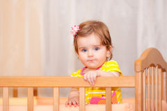 Small child with a hairpin standing in crib. Stock Photo