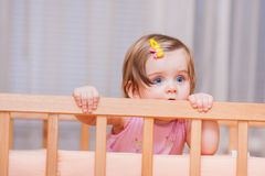 Small child with a hairpin standing in crib. royalty free stock photography