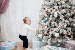 Small child hangs Christmas balls on the  tree Royalty Free Stock Photography