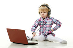 Small child in headset with laptop. Royalty Free Stock Image