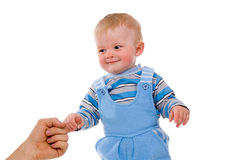 A small child is held by the hand of the parents stock images