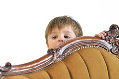The small child hides behind a sofa and looks out Royalty Free Stock Images