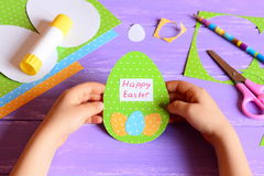 Small child hold a Easter card in hands. Child made Happy Easter greeting card in egg shape. Imagination and creativity Royalty Free Stock Photos