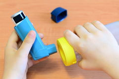 Small child holding asthma inhaler and spacer in his hands. Asthma spacer and aerosol inhaler Royalty Free Stock Images