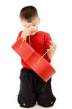 A small child is holding a box in the form of heart. On white background Stock Photos