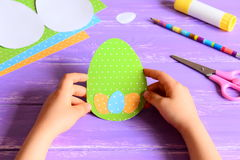 Small child holding a Easter card in hands. Child made Easter greeting card in egg shape royalty free stock photo