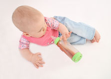 The small child holds a bottle laying on a floor Royalty Free Stock Photo
