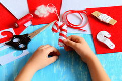 Small child holds Christmas felt candy cane in his hands. Child made a felt candy cane. Sewing supplies to create Christmas decor. Easy kids activity. Kids Stock Photography