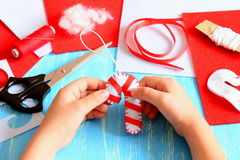 Small child holds Christmas felt candy cane in his hands. Sewing supplies to make Christmas tree decorations Royalty Free Stock Photography