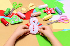 Small child holds a felt Christmas snowman in hands. Child shows Christmas ornament crafts. Beautiful felt Christmas tree ornament Royalty Free Stock Image