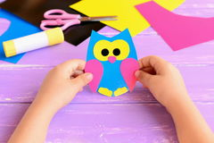 Small child holds paper owl in his hands. Child shows owl crafts. Colored paper sheets, scissors, glue stick. Royalty Free Stock Photography