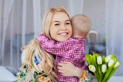 A small child hugs mom and gives flowers. The concept of childhood, education, family.  stock photos