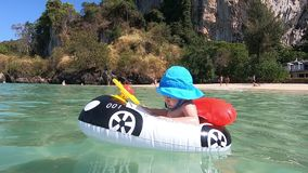 A small child in an inflatable boat or mattress in the shape of a car swims against a tropical sandy beach. On the baby blue panam