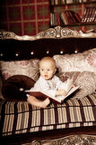 Small child in the interior reading a book. Smiling baby in the Stock Photo