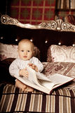 Small child in the interior reading a book. Smiling baby in the Stock Image